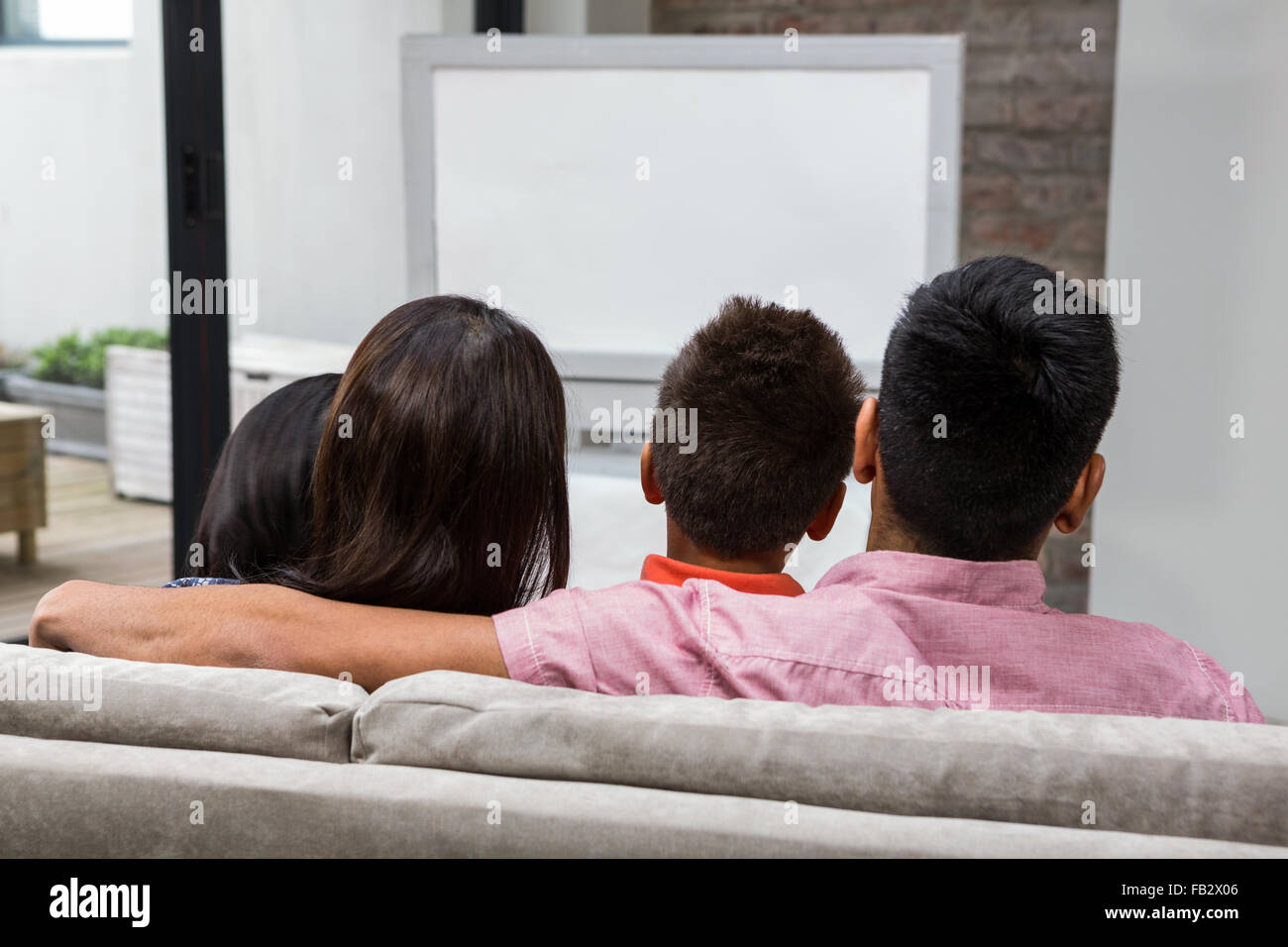 Happy family watching tv on the sofa - Stock Image