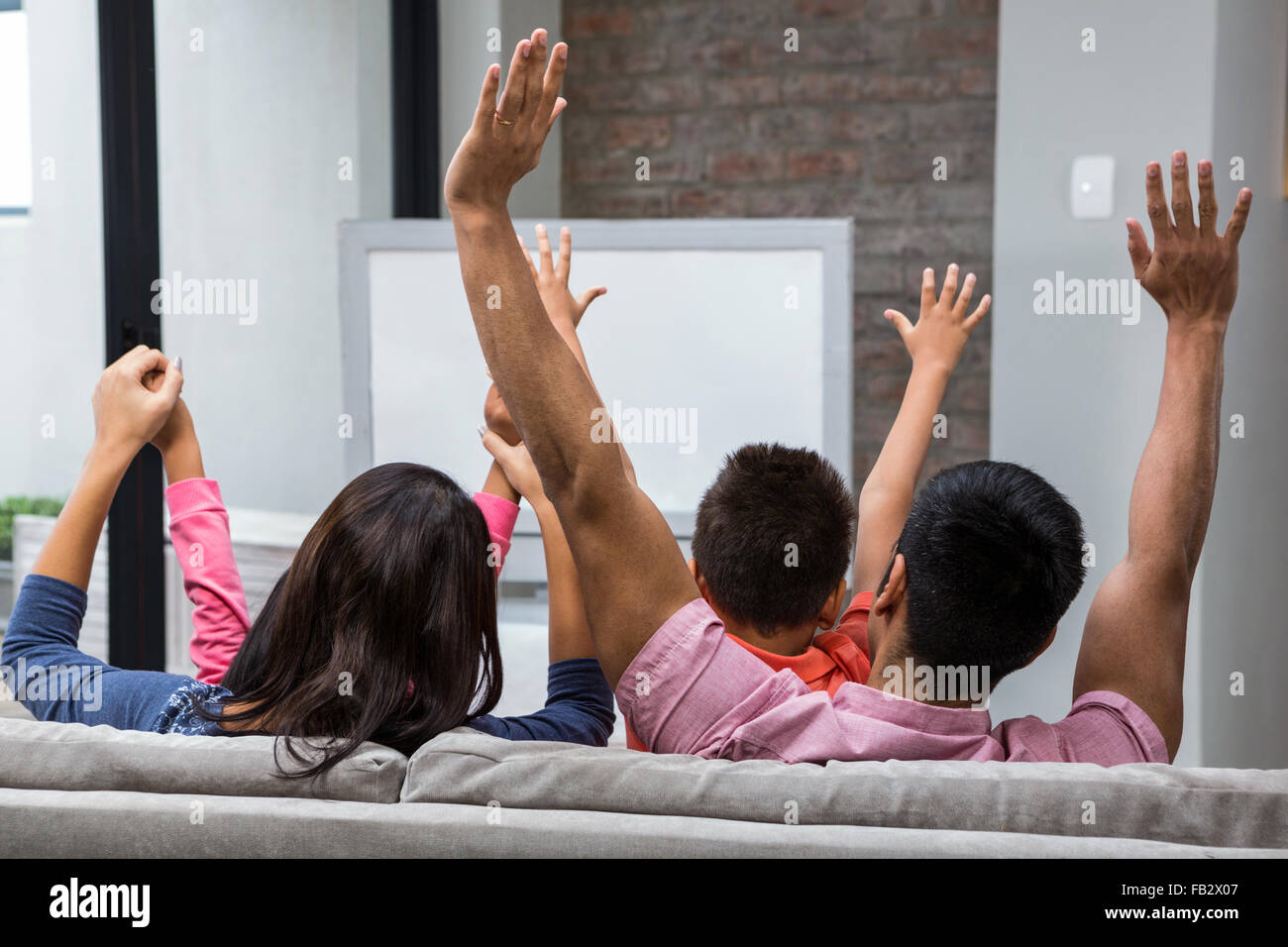 Happy family rejoicing while watching tv on the sofa - Stock Image