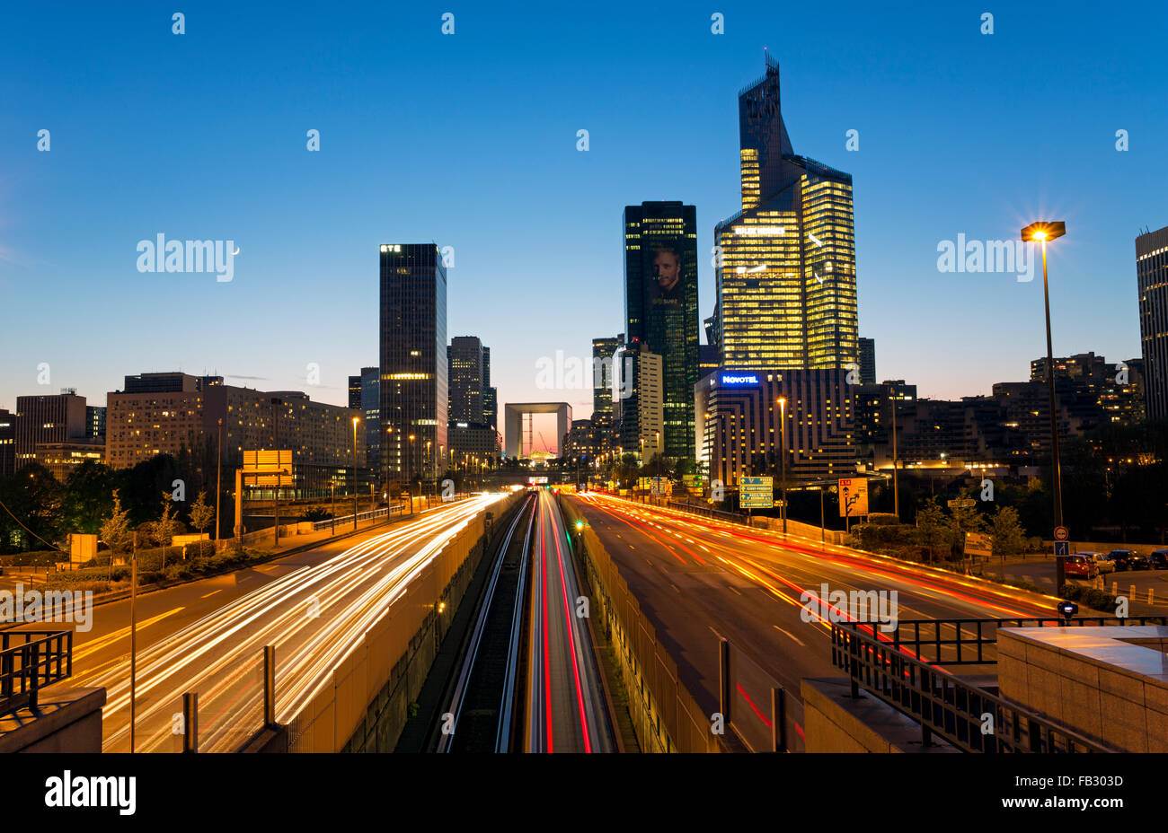 Paris road at night leading towards La Grande Arche and modern office buildings at La Defense, Paris, France - Stock Image