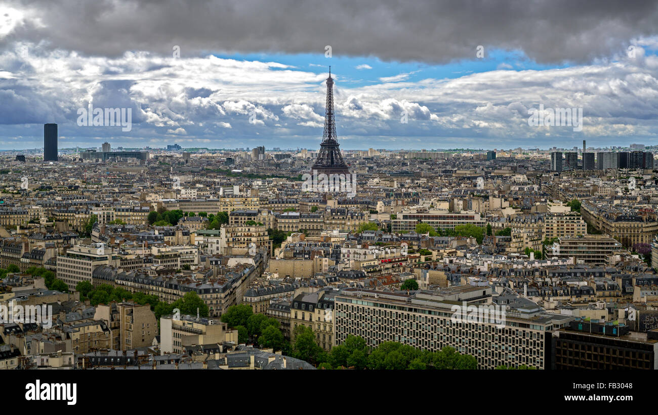 Eiffel Tower, elevated stormy city skyline viewed over rooftops, Paris, France, Europe Stock Photo