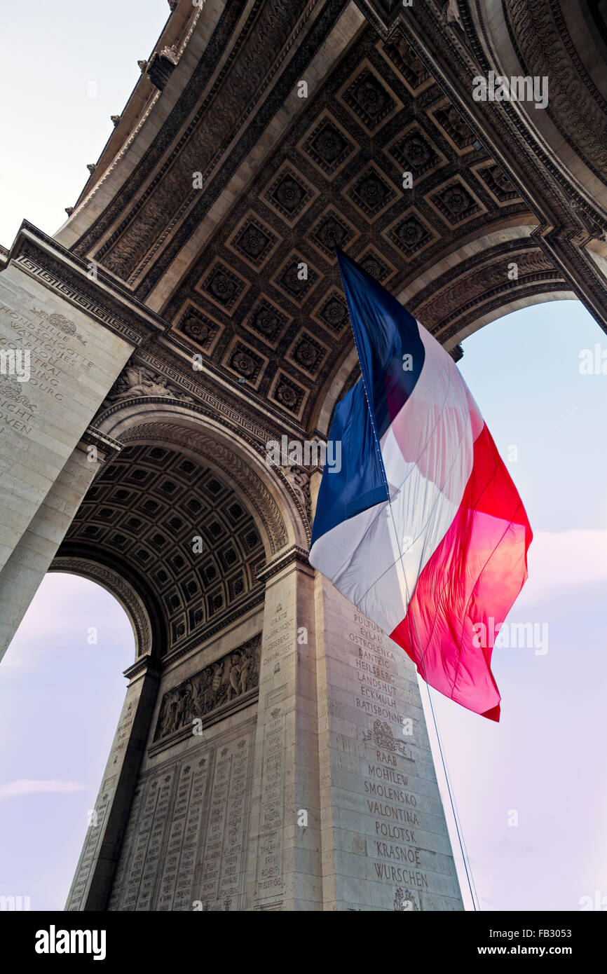 France, Paris, Etoile, French flag under Arc de Triomphe built by Napoleon - Stock Image