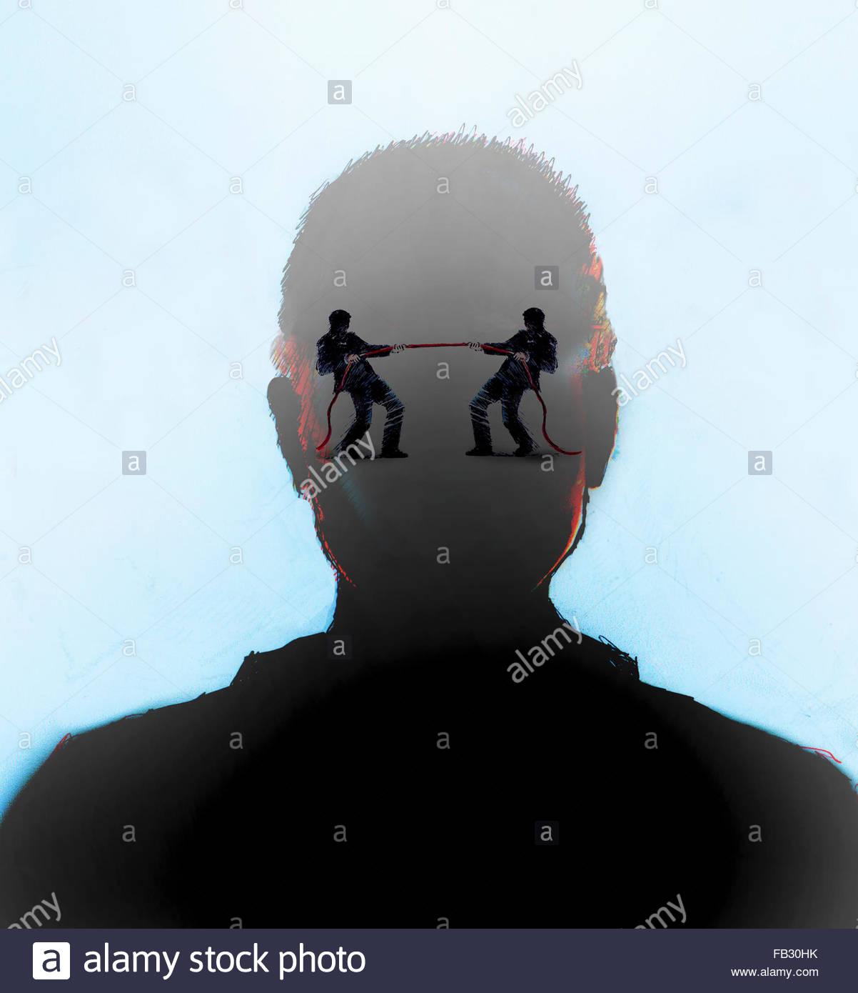 Businessmen in tug of war inside of man's head - Stock Image