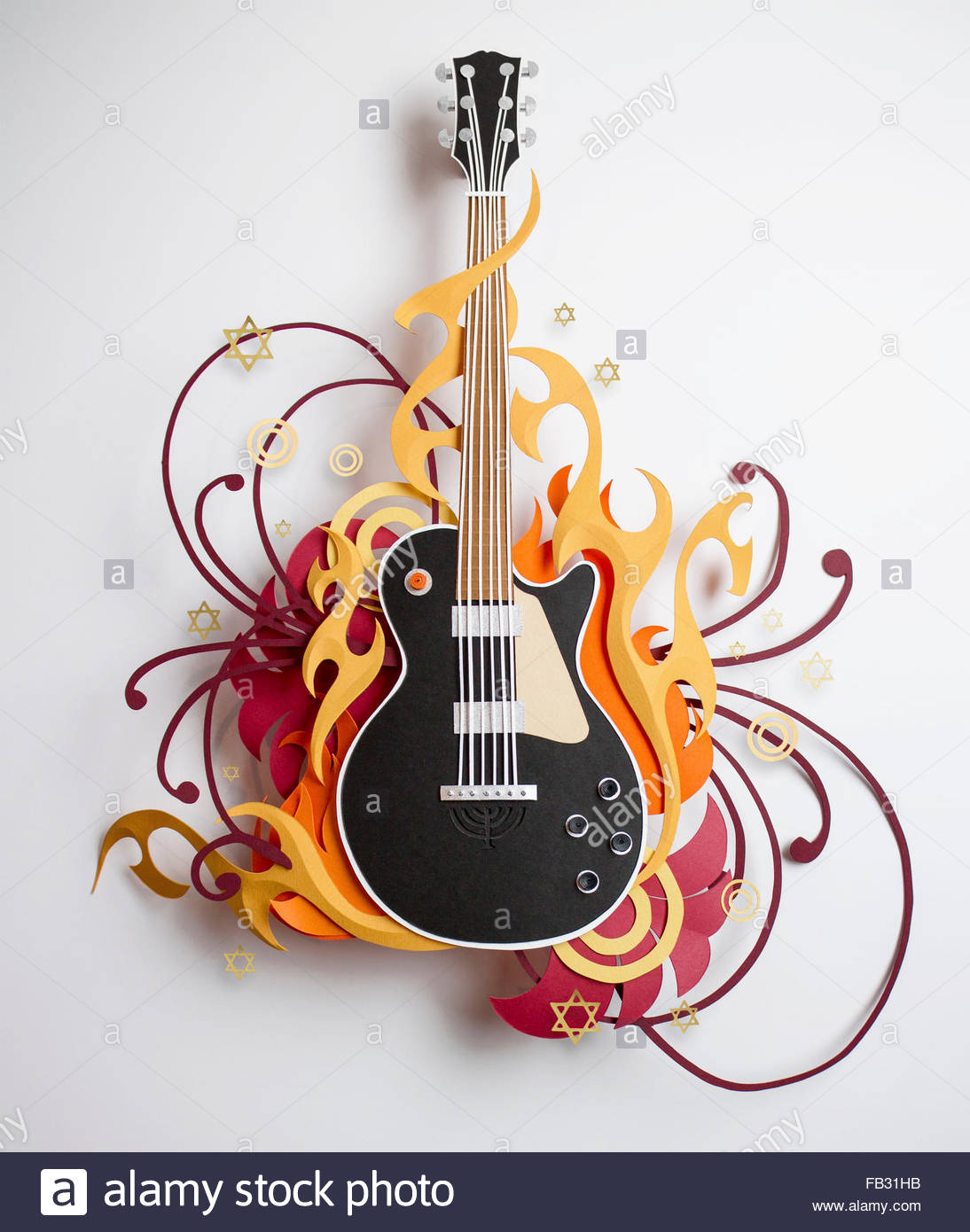 Stars and swirls surrounding paper craft guitar - Stock Image