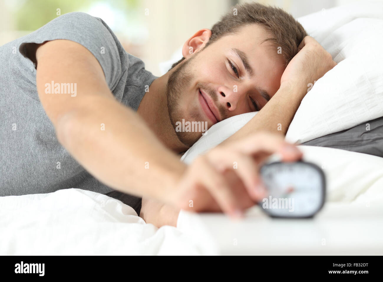 Happy wake up of a happy man lying on the bed and stopping alarm clock - Stock Image