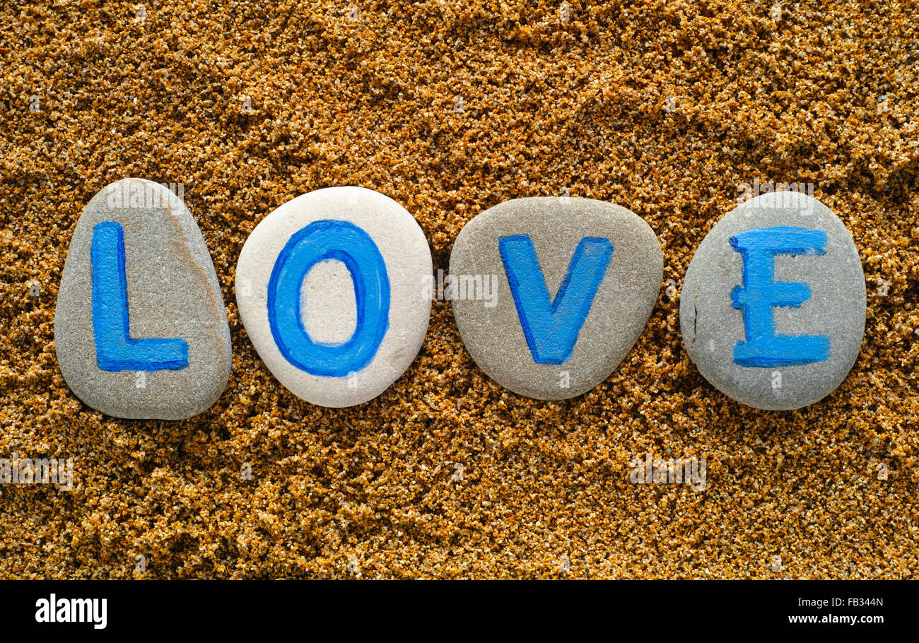 Word Love spell out from stones with letters on sea sand