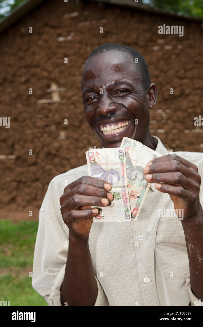Happy Kenyan farmer holding banknotes earned by selling milk from his cow. Kenya. - Stock Image