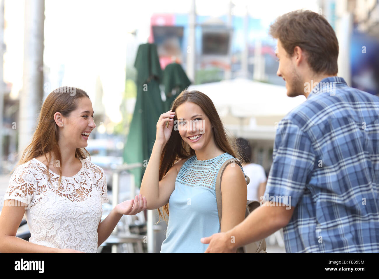 Candid girl with a friend flirting with a boy in the street - Stock Image