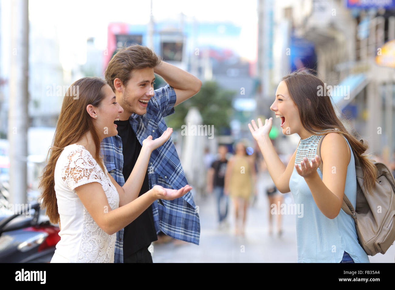 Three happy friends meeting in the street of a big city - Stock Image