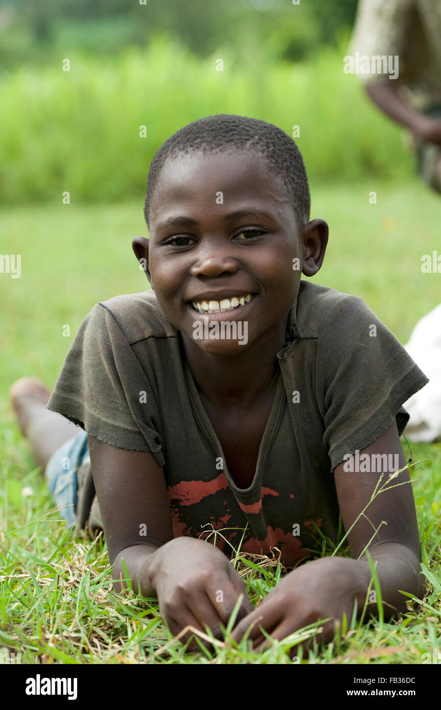 Young Kenyan boy laid on grass, smiling. Stock Photo
