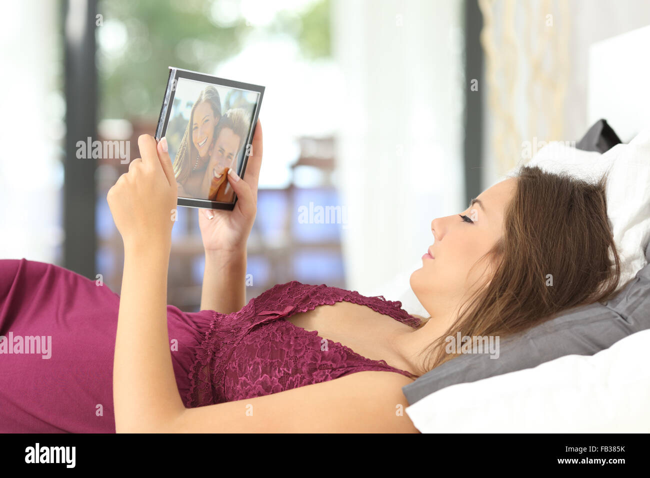 Longing woman looking a picture of her boyfriend in a frame on the bed at home - Stock Image