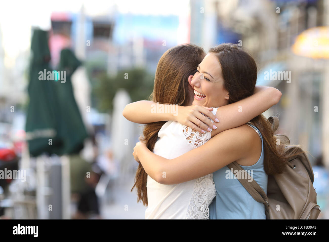 Happy meeting of two friends hugging in the street - Stock Image