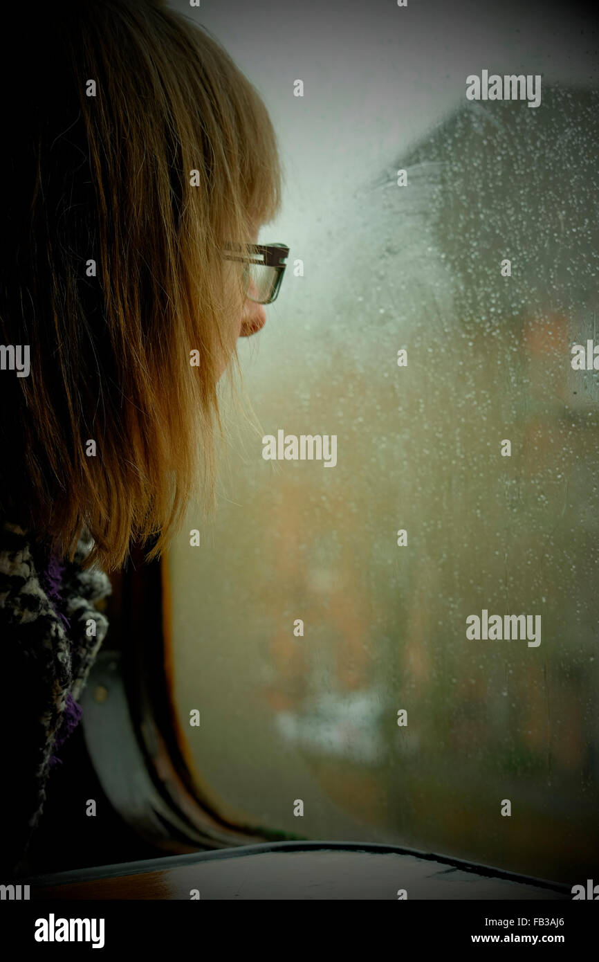 Young woman wearing glasses looking thoughtfully out through a misted up and rain covered train window whilst at Stock Photo