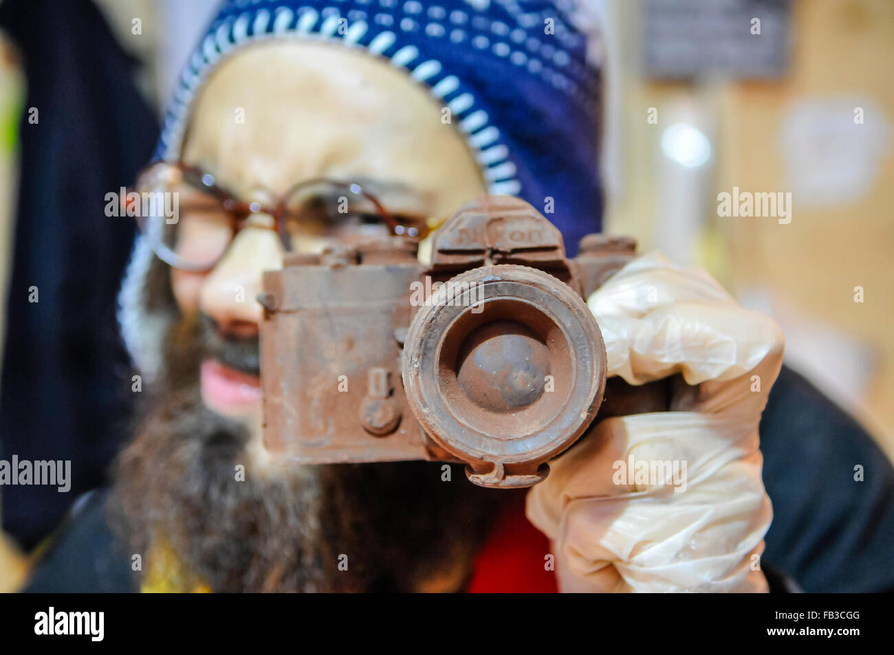 A market stall holder holds up an SLR camera made entirely from chocolate. - Stock Image