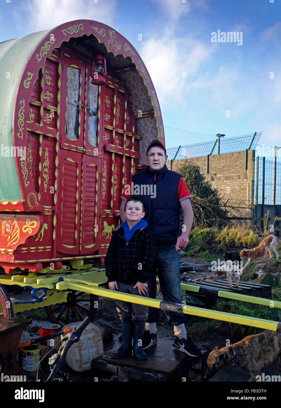 An Irish traveler father and son stand outside their old fashioned horse drawn caravan or covered wagon, - Stock Image
