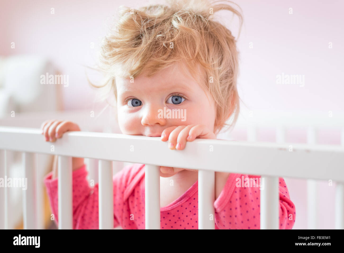 One year old baby in her cot - Stock Image