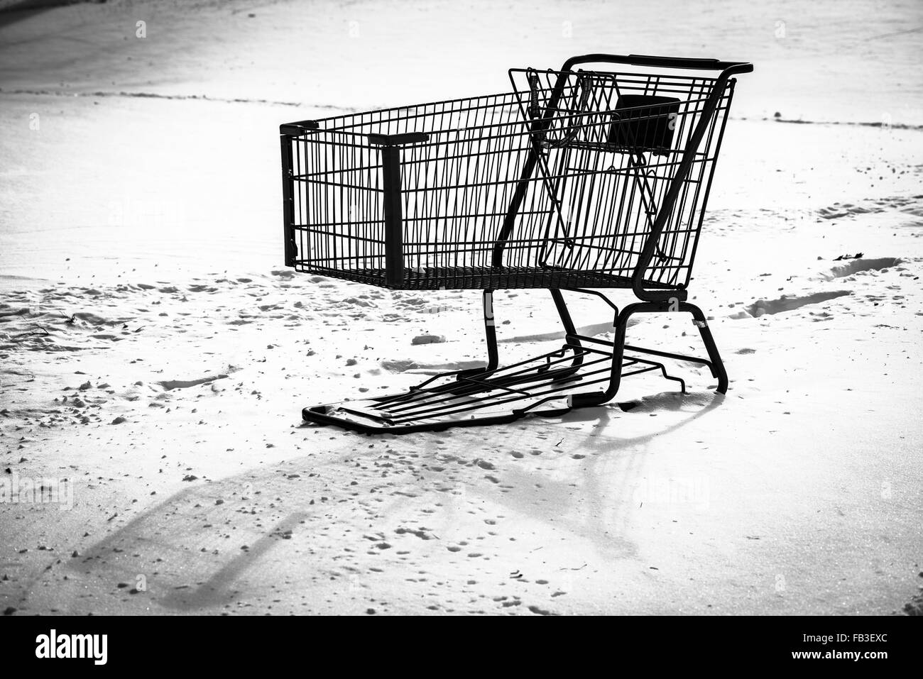 High contrast black and white image of shopping cart abandoned in snow by the shopper. - Stock Image