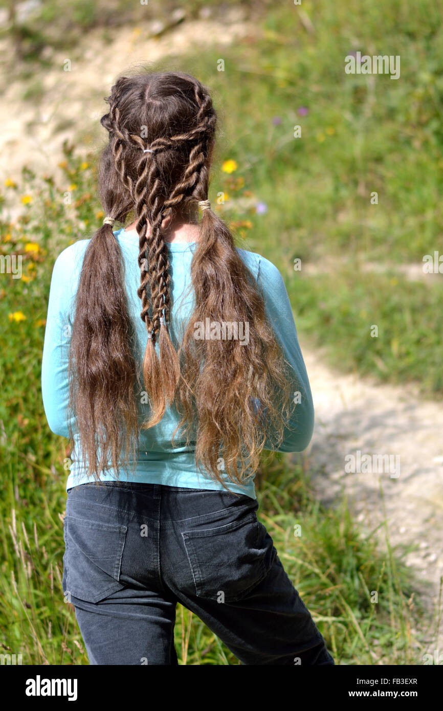 Girl with renaissance hairstyle of pigtails and rope braids. A pre-teen girl with exceptionally long golden hair Stock Photo