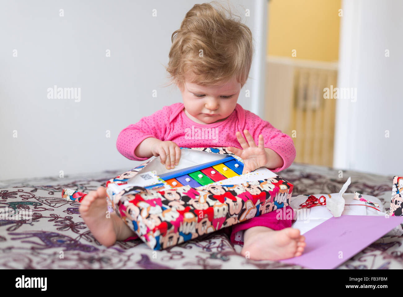 One year old baby unwrapping birthday present - Stock Image