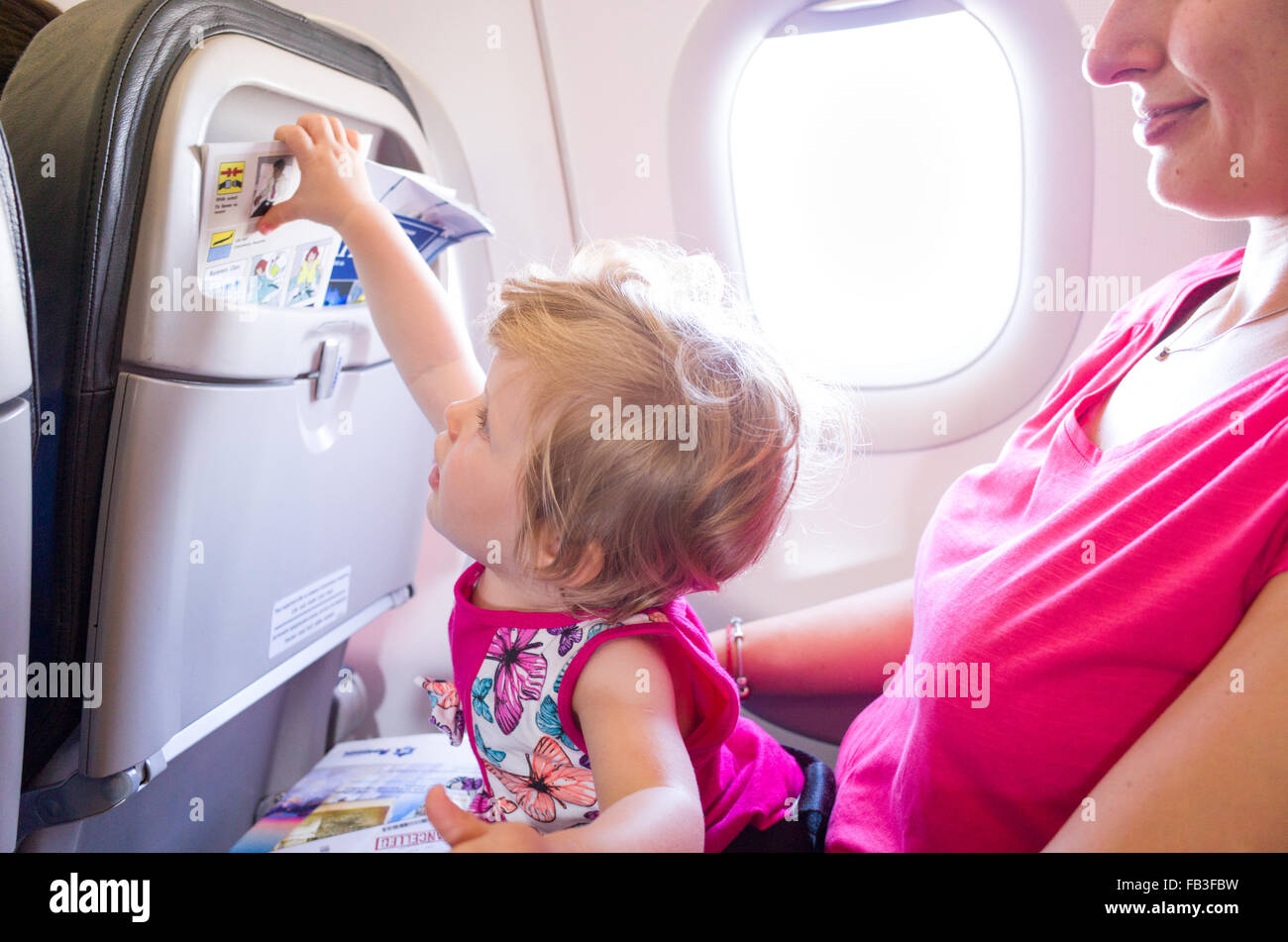 Mother travelling with one year old baby on an aeroplane - Stock Image