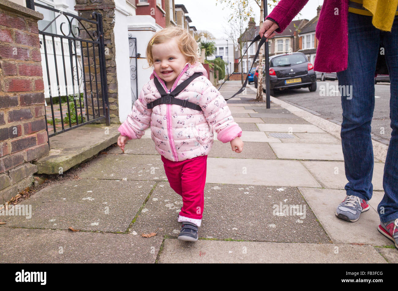 Toddler walking down the street held with a safety harness, London, UK - Stock Image