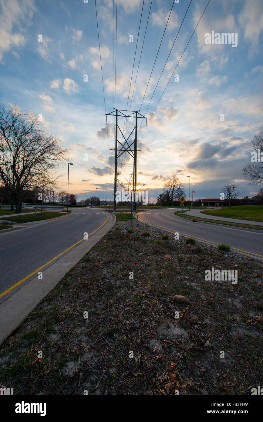 View of opposite directions of a one-way divided street from the divider as the sun was setting on the horizon - Stock Image