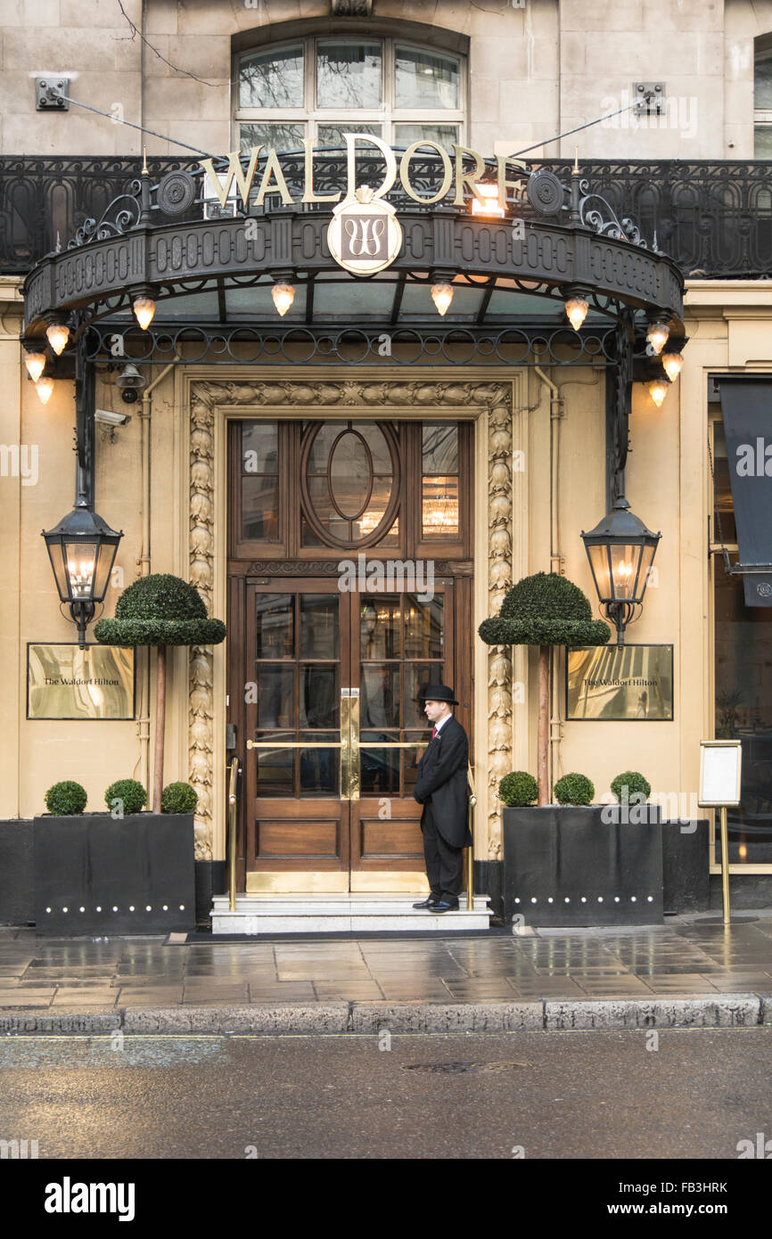 A Bell Boy standing outside the famous Waldorf Hotel on Aldwych in London's West End, UK. - Stock Image