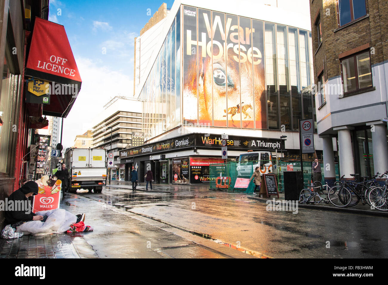Homeless man huddled under awning in wet London street outside the New London Theatre on Drury Lane, which is showing - Stock Image