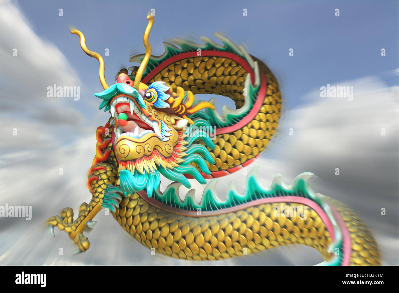 conceptual art : action zoom blurring effect of china dragon statue flying in the sky background - Stock Image