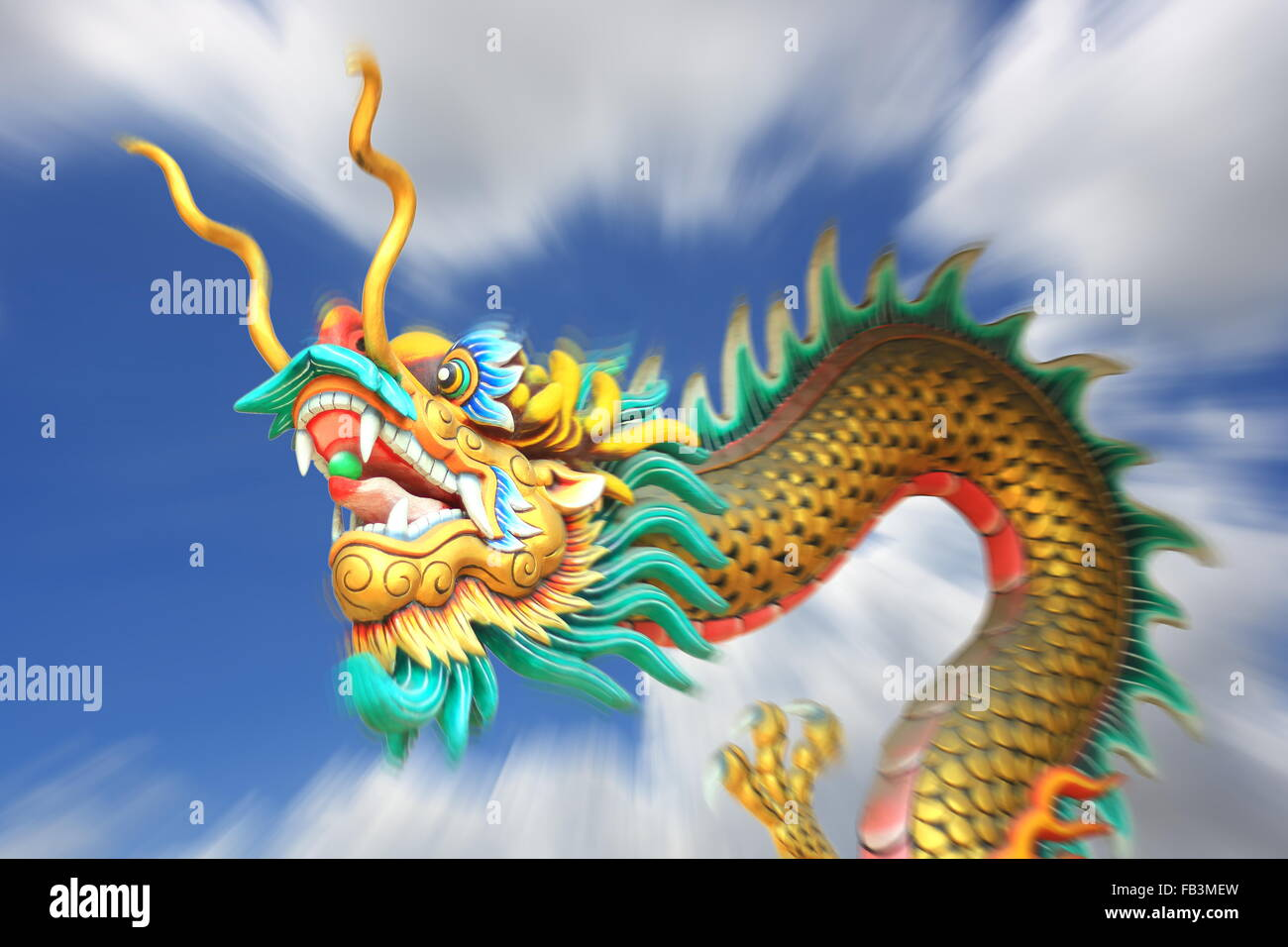 conceptual art : zoom blurring effect of china dragon statue flying in the sky. - Stock Image