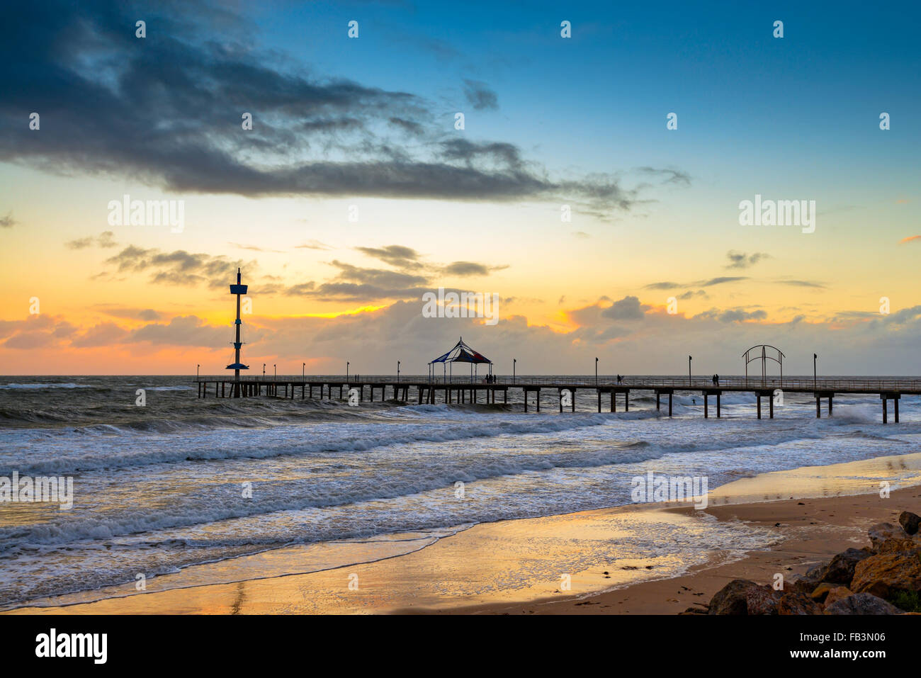 Surfer on Brighton Jetty at sunset on a stormy weather, South Australia - Stock Image