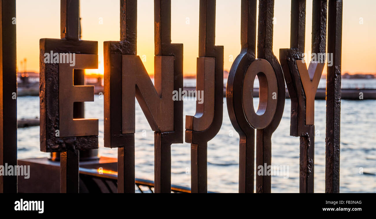 The word 'Enjoy' inset into iron railings at the World Financial Plaza with a sunset over the Hudson river - Stock Image