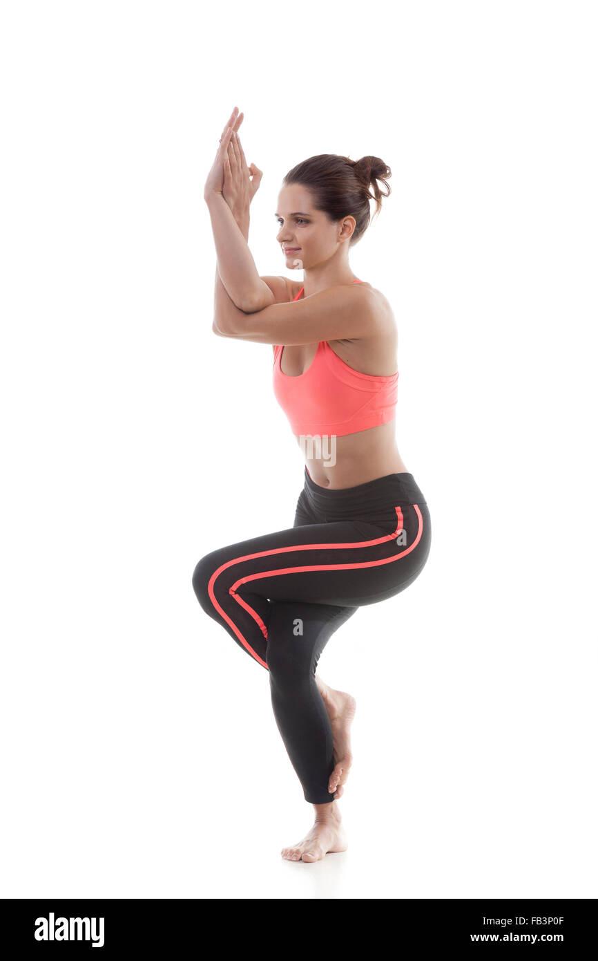 Sporty yoga girl on white background in garudasana (Eagle Pose) - Stock Image