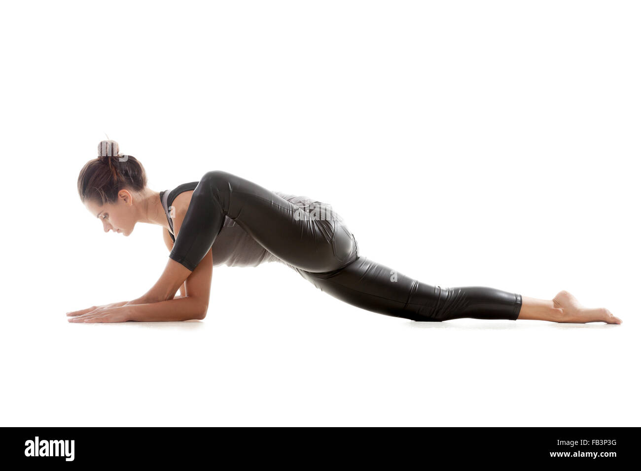 Sporty yoga girl on white background exercises, the left knee is bent over the left ankle - Stock Image