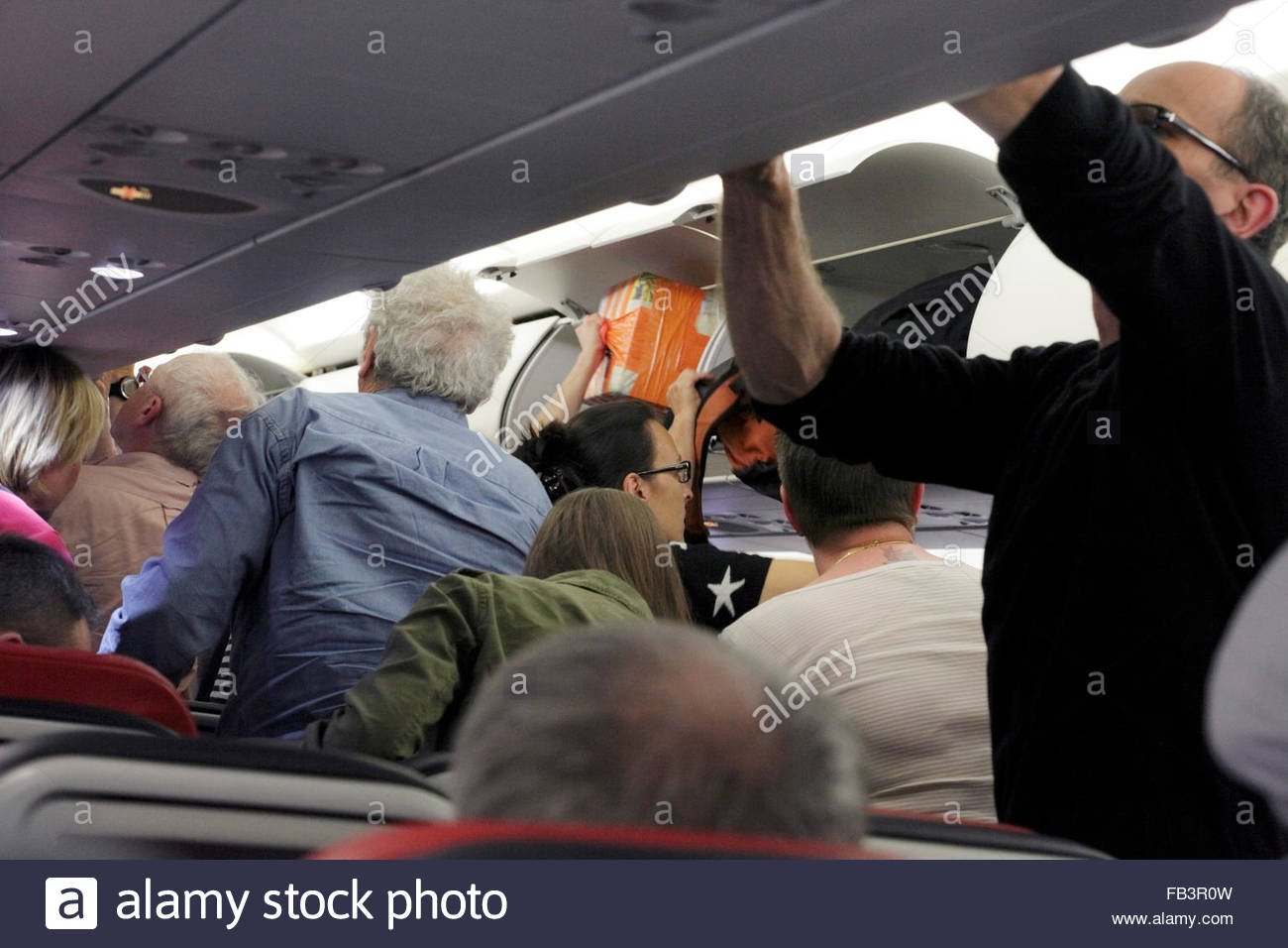 airplane passenger getting their overhead luggage - Stock Image
