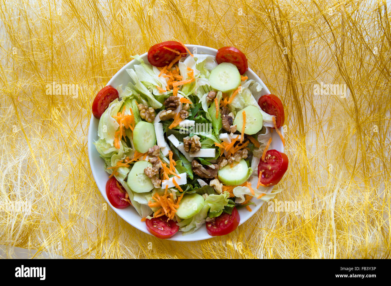 Particular of mix salad with cucumbers, walnuts, tomatoes, carrots, lettuce and feta - Stock Image