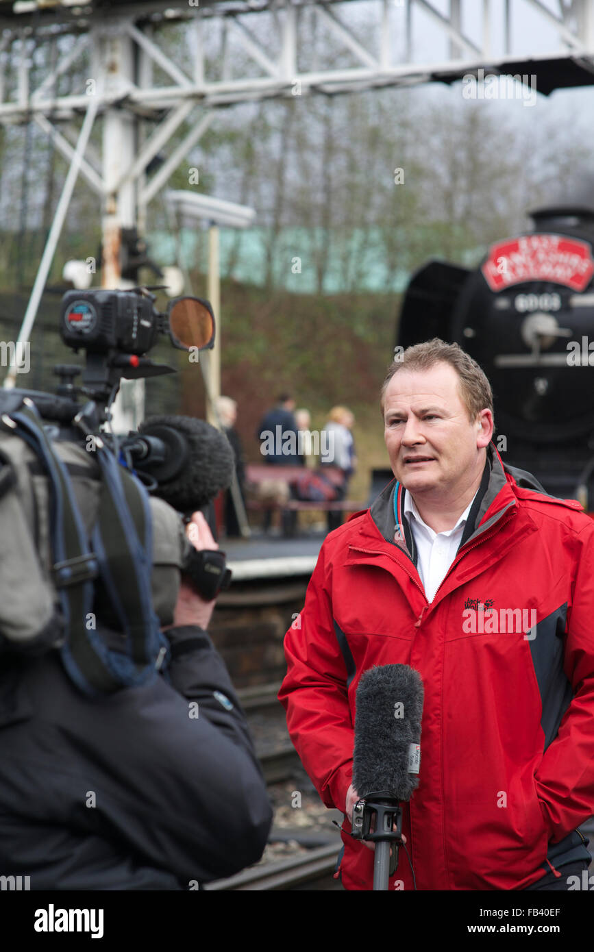 Sky tv reporter delivering piece to camera in front of flying Scotsman on the east lancashire railway in bury lancashire - Stock Image
