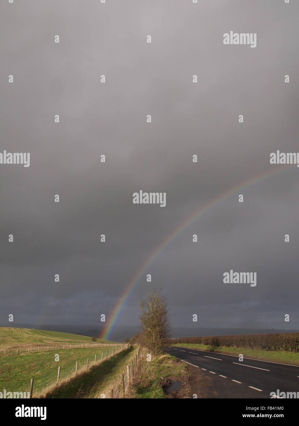 rainbow arc, road in distance grey stormy sky, rain showers - Stock Image