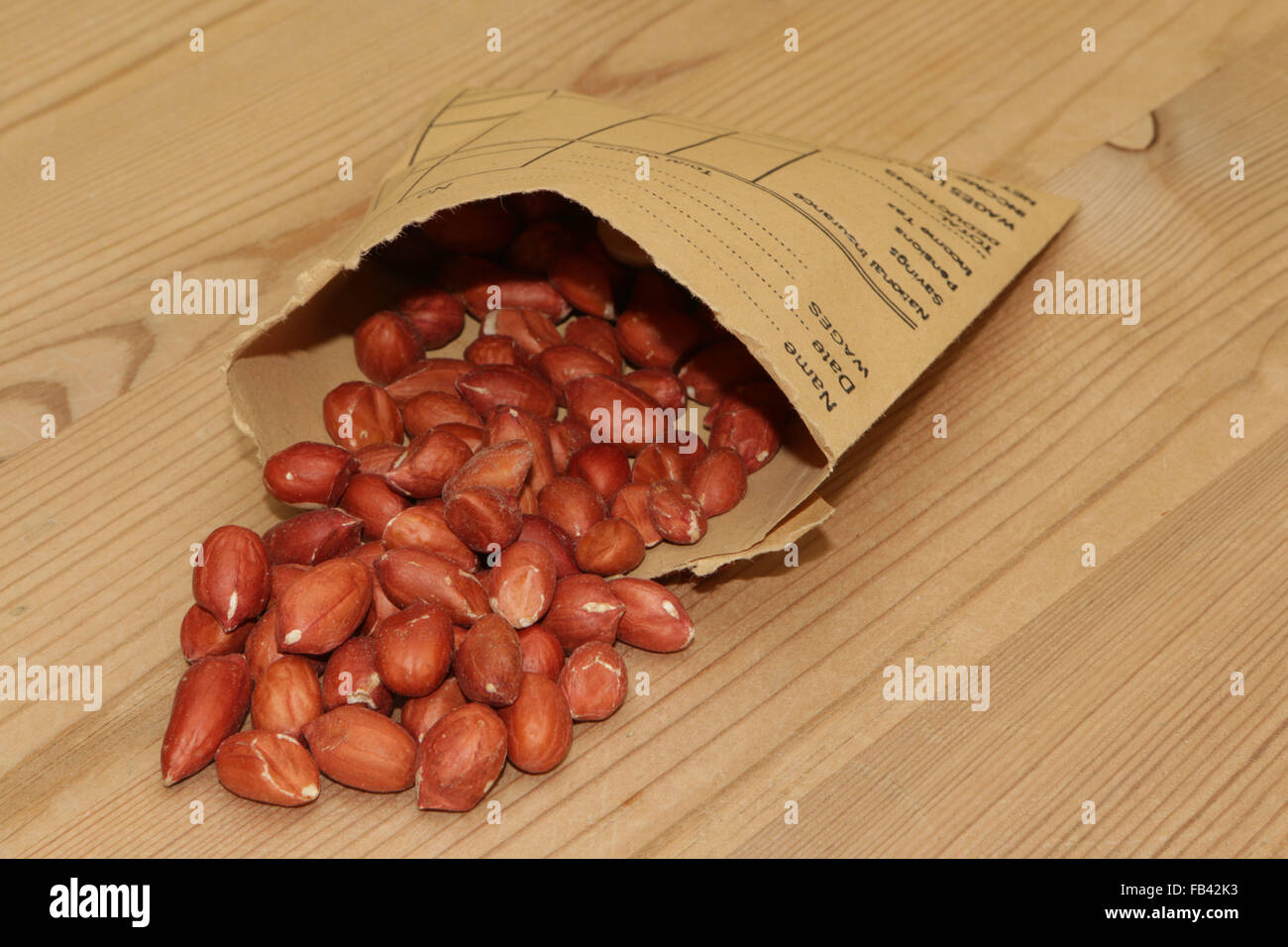 Wage packet containing peanuts - Stock Image