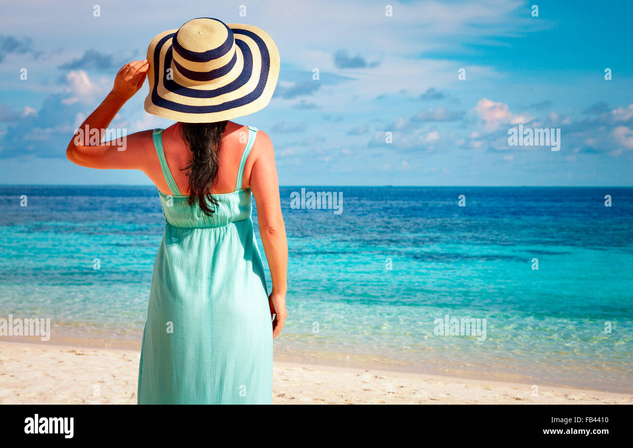Beach vacation. Girl walking along a tropical beach in the Maldives. - Stock Image