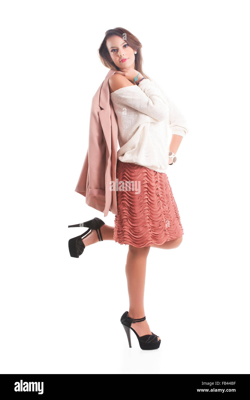 Portrait Of Attractive Young Woman Holding Coat Over White Background - Stock Image