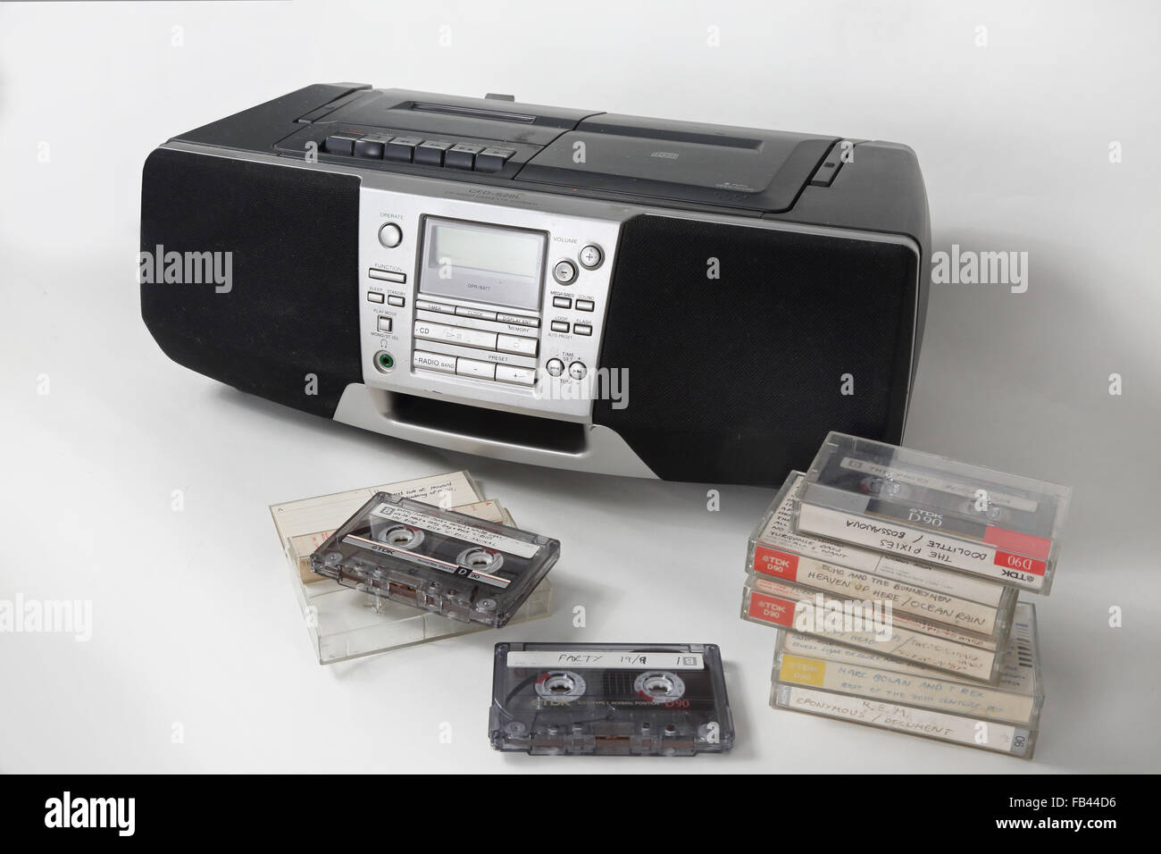 Home recorded cassette tapes stacked up in front of a 1990s style cassette, radio and and CD player - Stock Image
