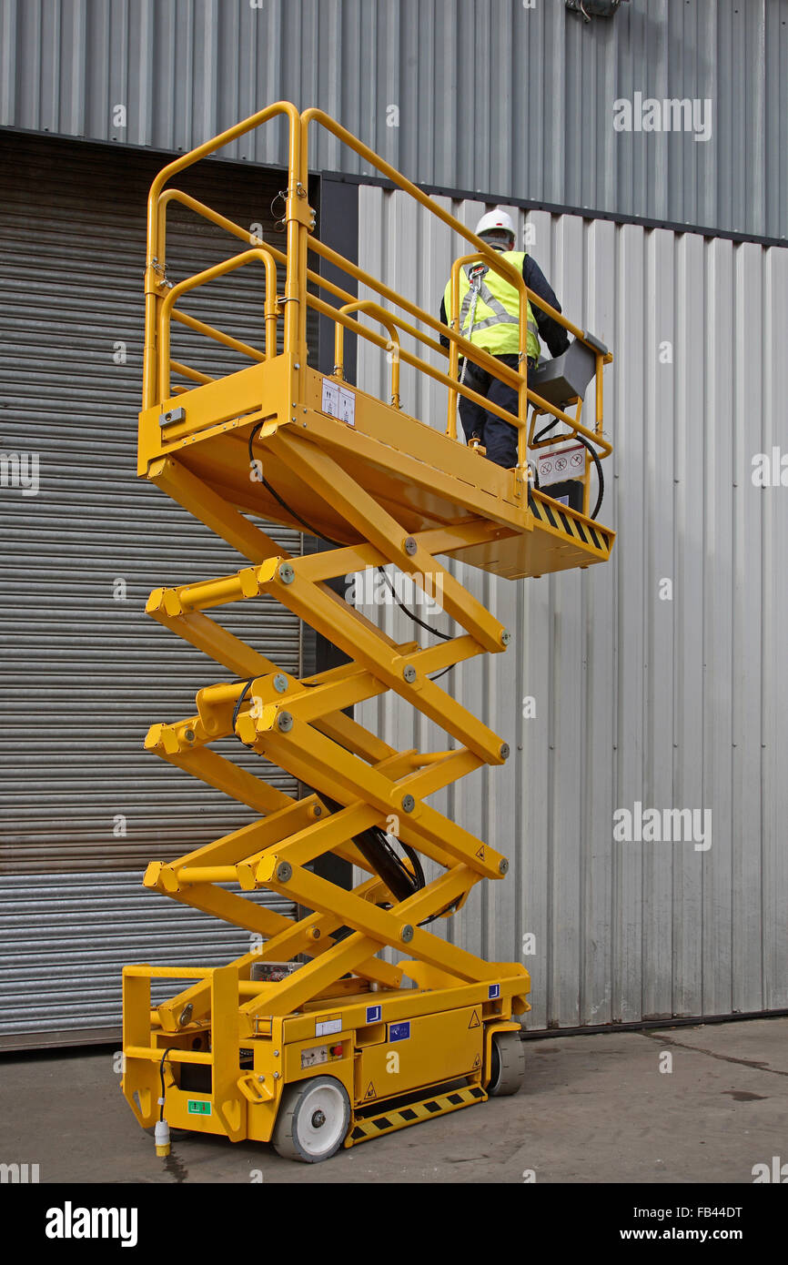 A worker elevates a small industrial scissor lift to gain high level access for maintenance on a warehouse - Stock Image
