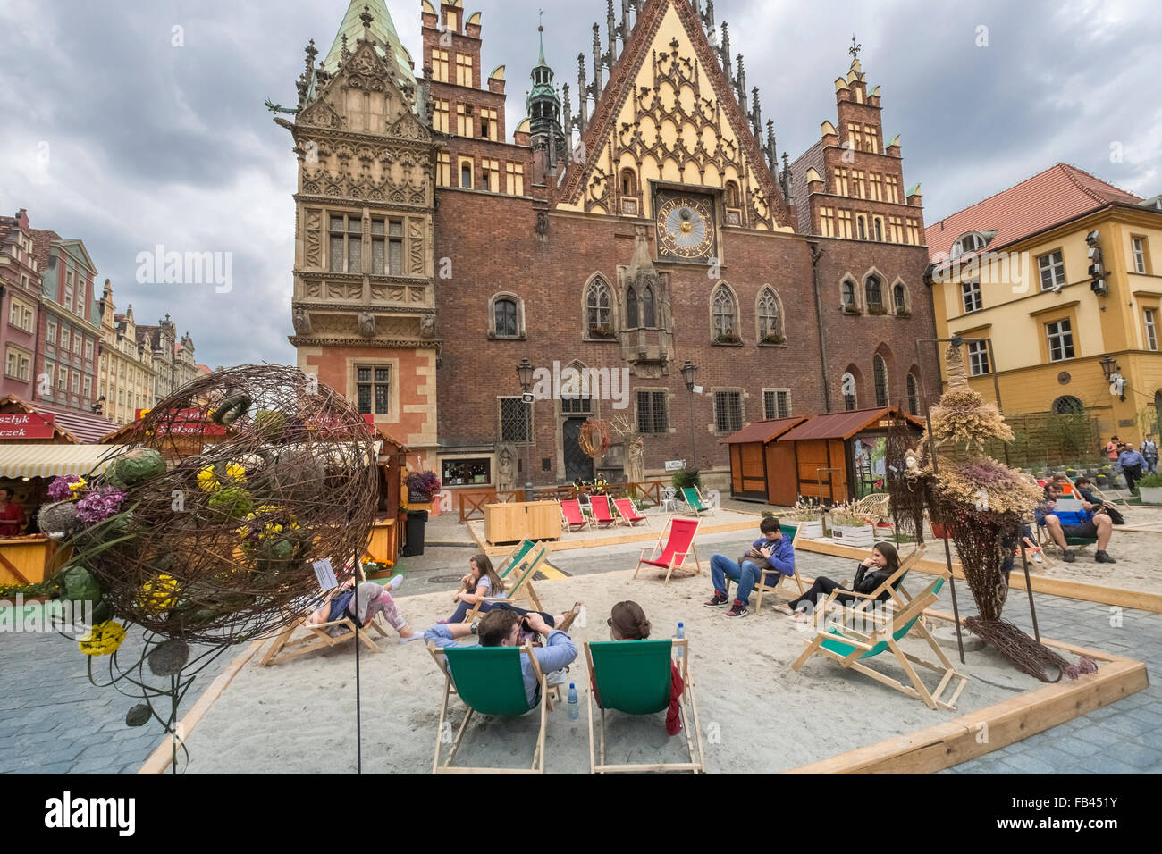 Tourists sitting outside East side of Wroclaw Gothic Town Hall, Market Square, Old Town, Wroclaw, Poland - Stock Image