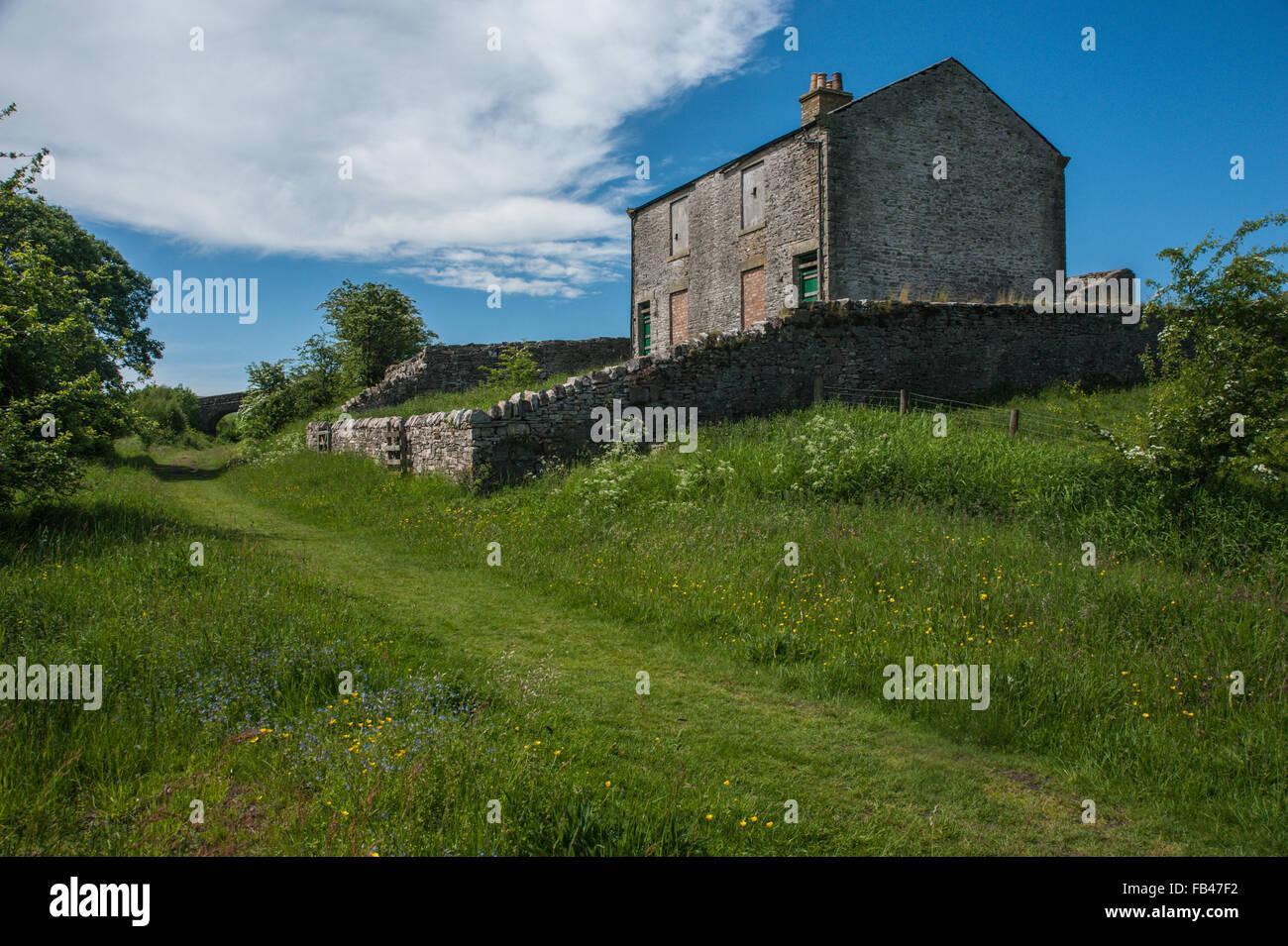 Derelict houses beside dismantled railway line - Stock Image