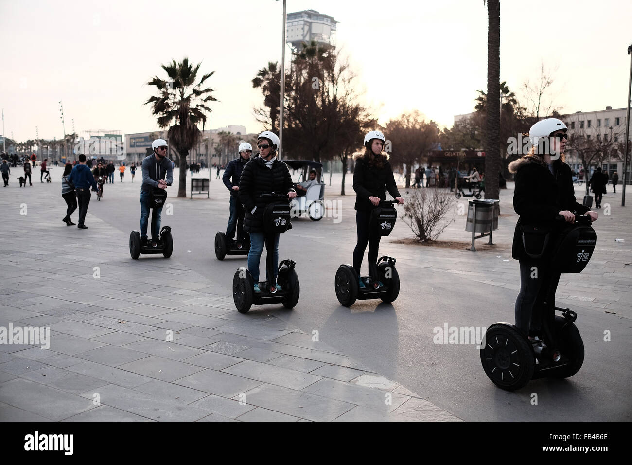 5 helmeted tourists traveling on Segway's on Barcelona's waterfront in Barceloneta. - Stock Image