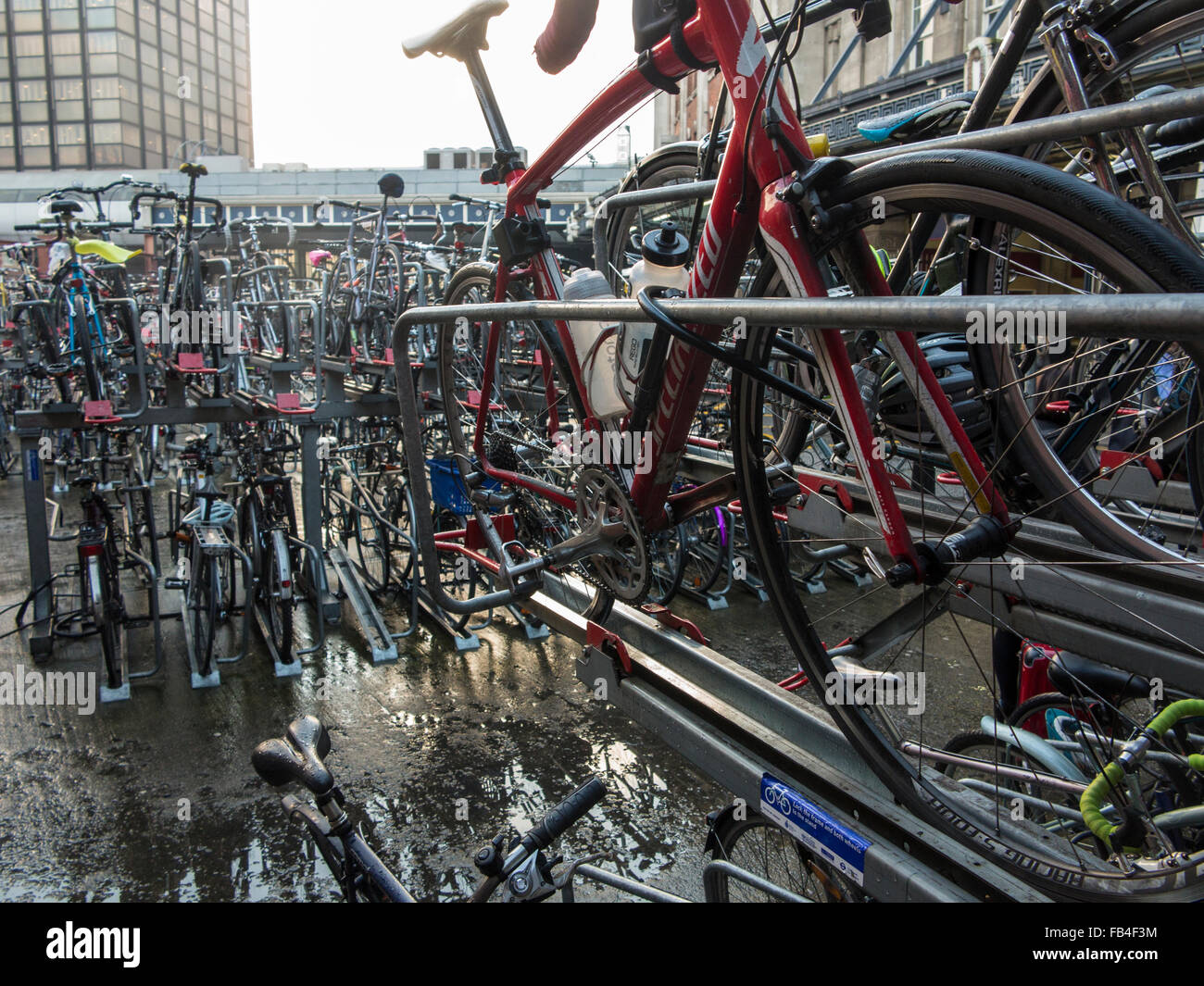 Commuter bicycles stacked high at Waterloo station in London - Stock Image