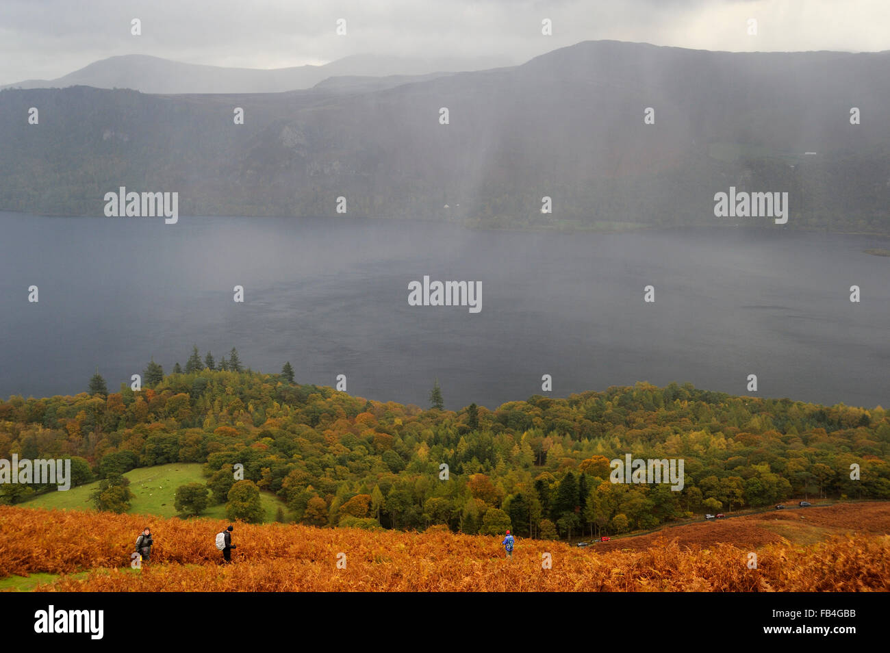 View over Derwentwater from Catbells, with rain squall over the lake and walkers decsending through bracken covered - Stock Image