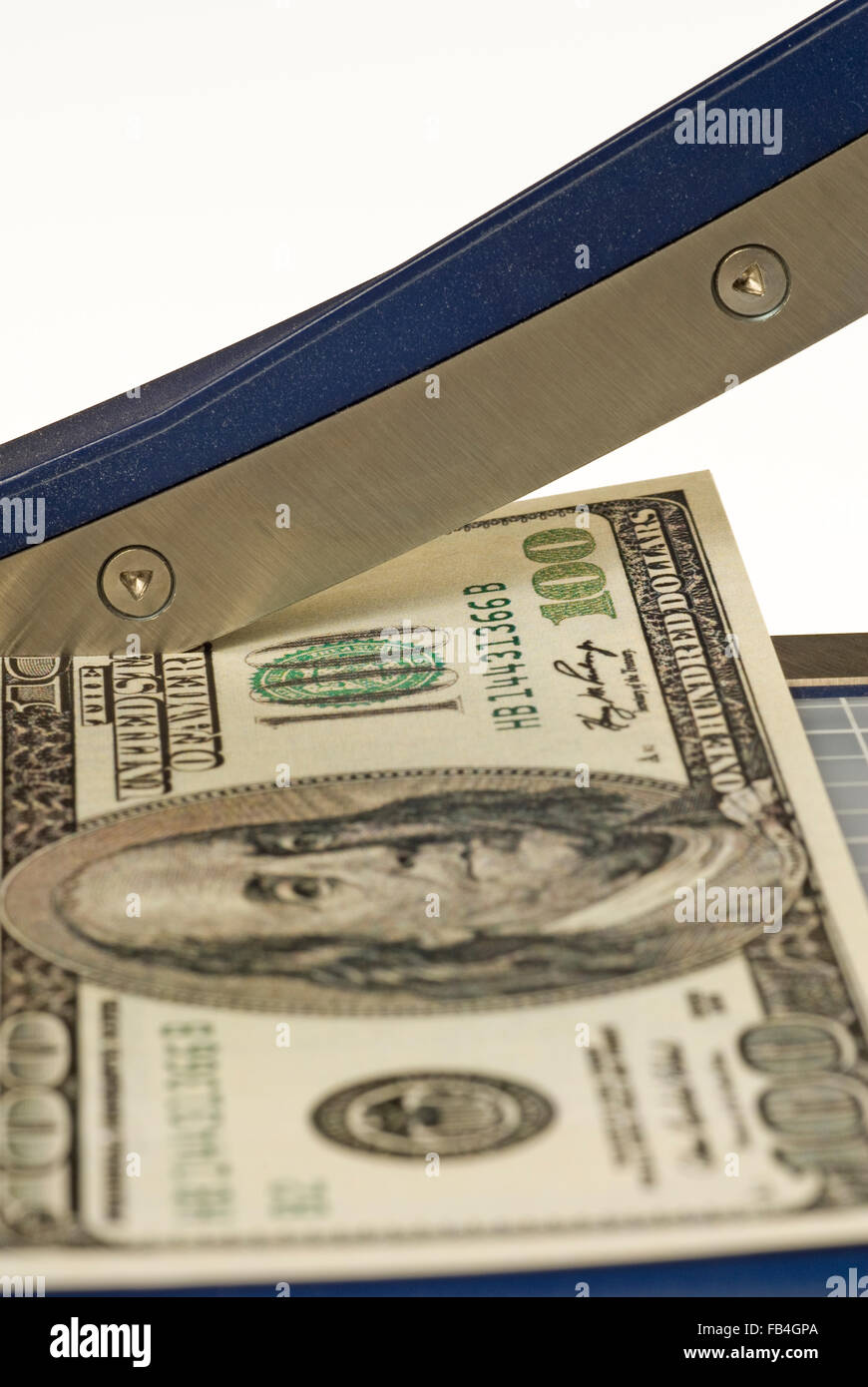 Paper Cutter Cutting a One Hundred Dollar Bill - Stock Image