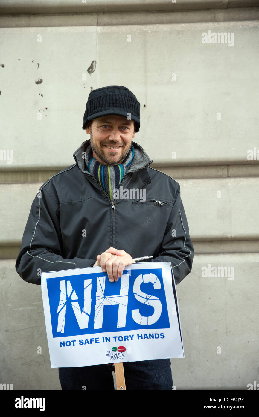 London, UK. 9th January, 2016. A protester with a placard reading 'NHS Not Safe in Tory Hands' before the - Stock Image