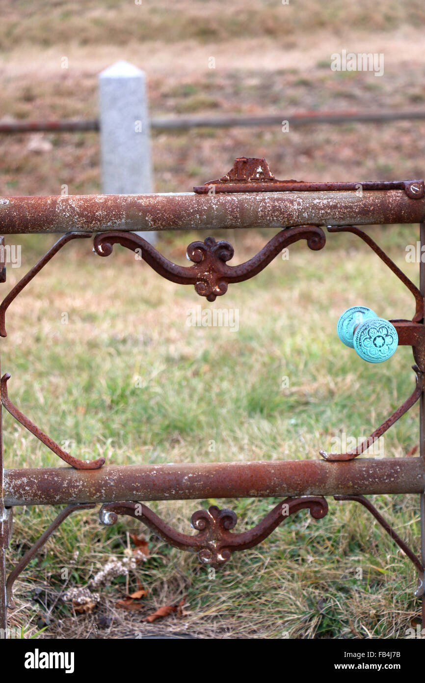 19th Century iron fence with oxidized copper door handle found in a Nantucket, Massachusetts cemetery. - Stock Image